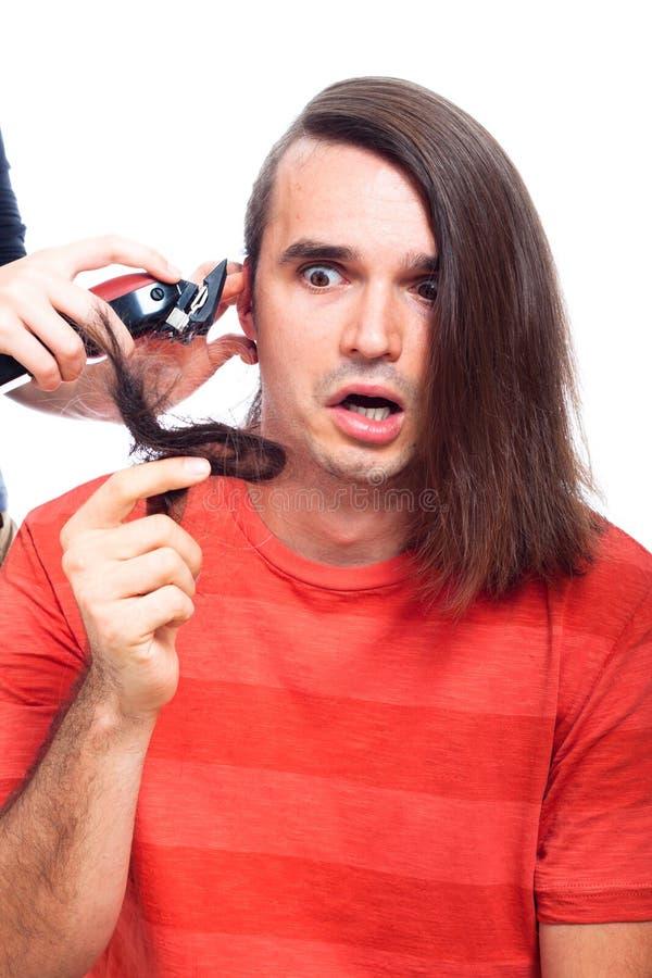 Geschokte mens die met haarsnoeischaar wordt geschoren stock foto