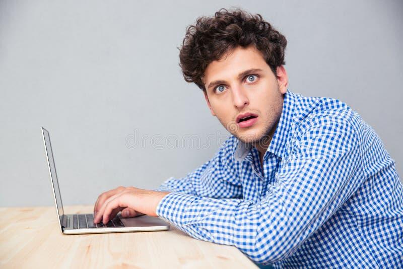 Geschokte mensenzitting bij de lijst met laptop royalty-vrije stock fotografie