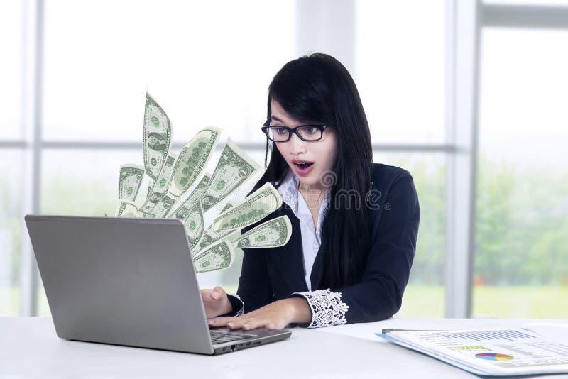 Geschokte onderneemster die geld laptop bekijken stock fotografie