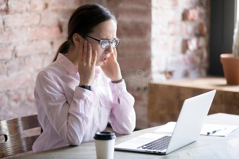 Geschokte onderneemster die laptop het scherm met vrees bekijken royalty-vrije stock fotografie