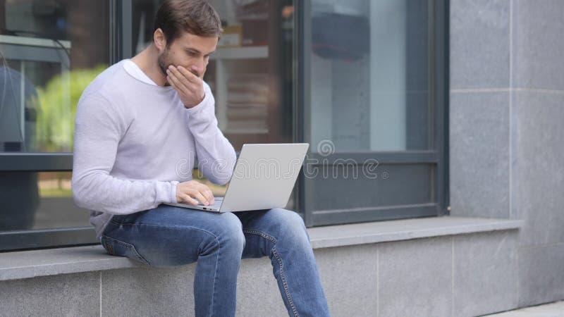 Geschokte, Overweldigde Knappe mens die Laptop met behulp van terwijl het Zitten op Treden buiten Bureau stock afbeeldingen