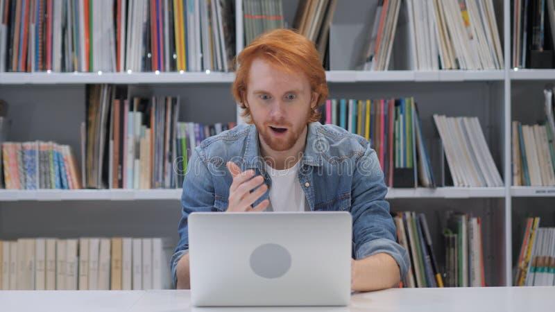 Geschokte, overweldigde mens met rode haren die aan laptop werken royalty-vrije stock fotografie