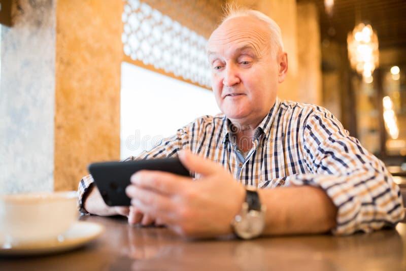 Geschokte rijpe mens die smartphone in koffie gebruiken stock afbeeldingen