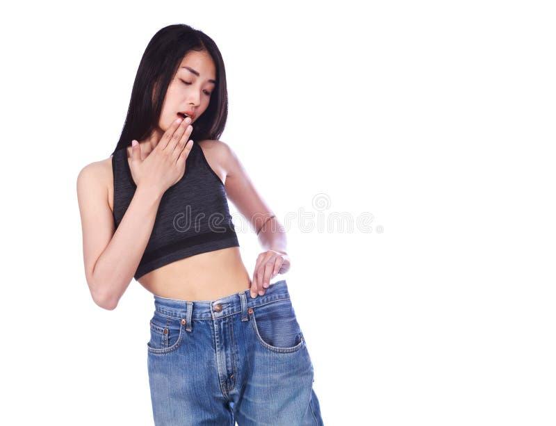 Geschokte slanke geschiktheidsvrouw in oude jeans na het verliezen gewichtsisol royalty-vrije stock foto's