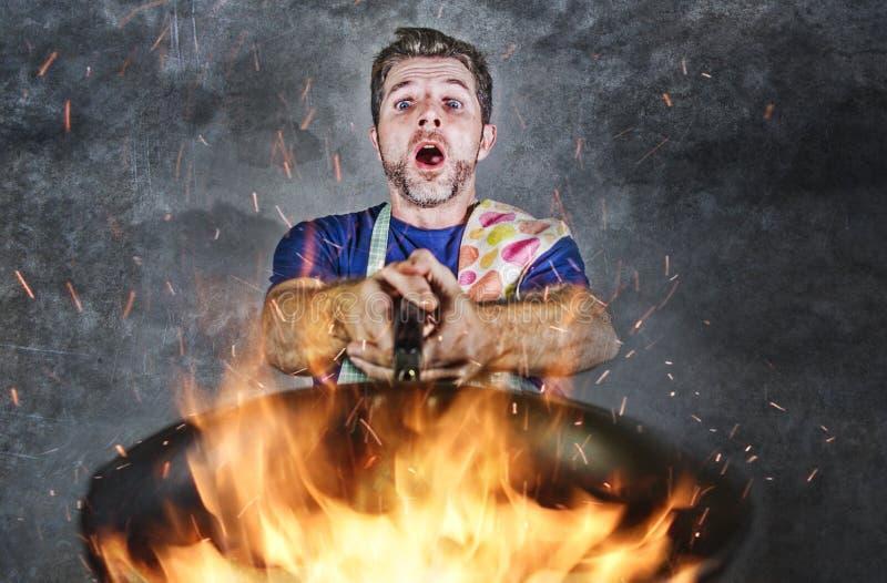 Geschokte slordige mens met de pan van de schortholding in brand die het voedsel in keukenramp en ongeschoolde en unexperienced v stock afbeeldingen