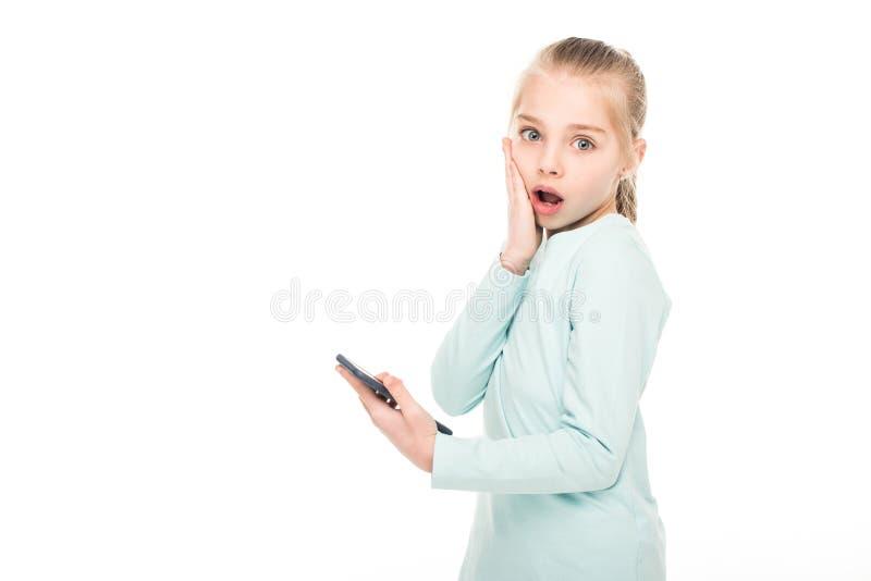 geschokte smartphone van de meisjeholding en het bekijken camera royalty-vrije stock afbeeldingen
