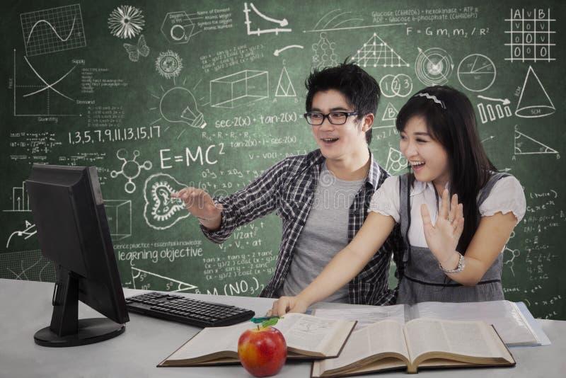 Geschokte studenten die bij monitor staren stock fotografie