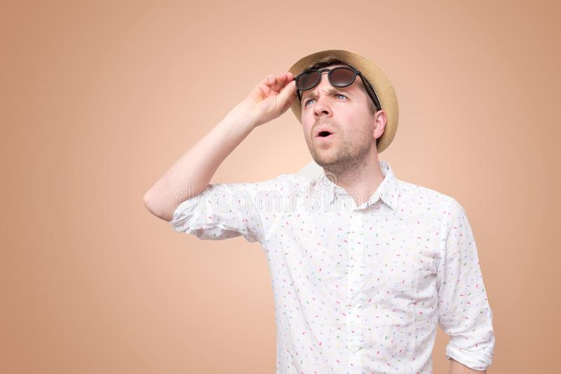 Geschokte verbaasde mens in de zomerhoed wat betreft zijn glazen royalty-vrije stock afbeelding