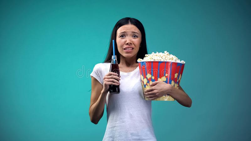 Geschokte vrouw die met kop die van popcorn op enge film letten, bruisend water houden stock fotografie