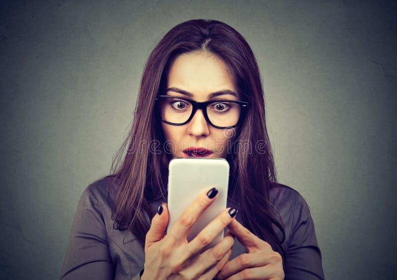 Geschokte vrouw die mobiele telefoon bekijkt stock afbeeldingen