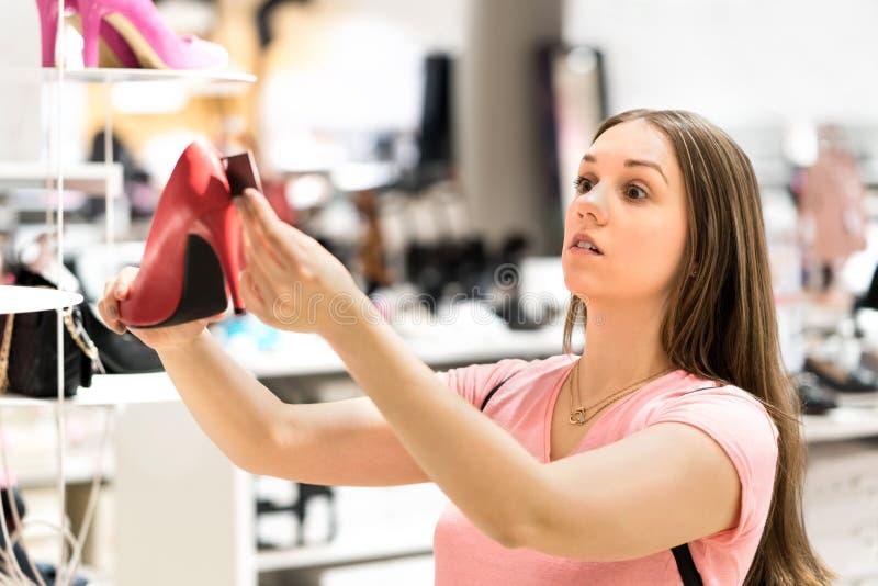 Geschokte vrouw die prijskaartje van te dure schoenen bekijken stock fotografie