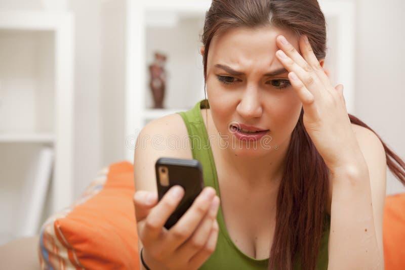 Geschokte vrouw die telefoon bekijkt royalty-vrije stock fotografie