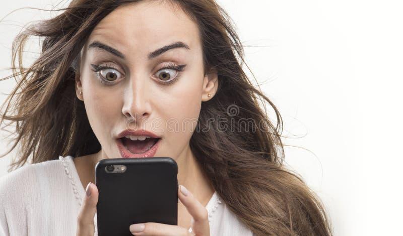 Geschokte vrouw die telefoon, Jong geschokt meisje bekijken het bekijken mobiel royalty-vrije stock foto's