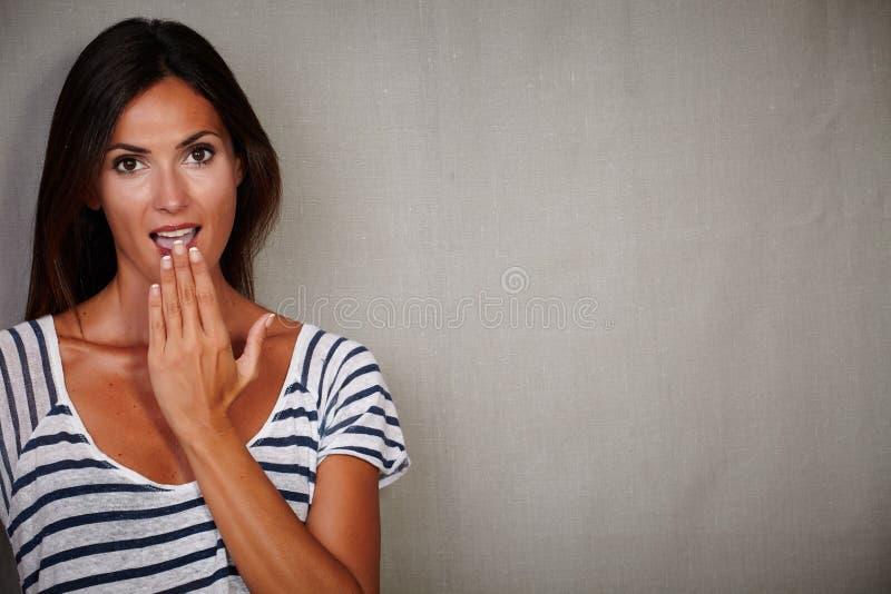 Geschokte vrouwelijke status tegen grijze achtergrond stock afbeeldingen