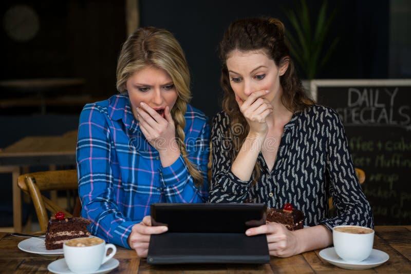 Geschokte vrouwen die tabletcomputer in koffiewinkel met behulp van stock afbeeldingen