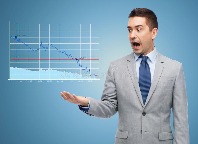 Geschokte zakenman die in kostuum aan grafiek kijken stock afbeelding