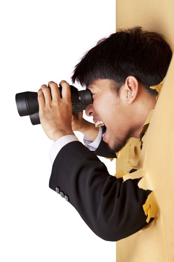 Geschokte zakenman die met verrekijkers kijkt stock afbeeldingen