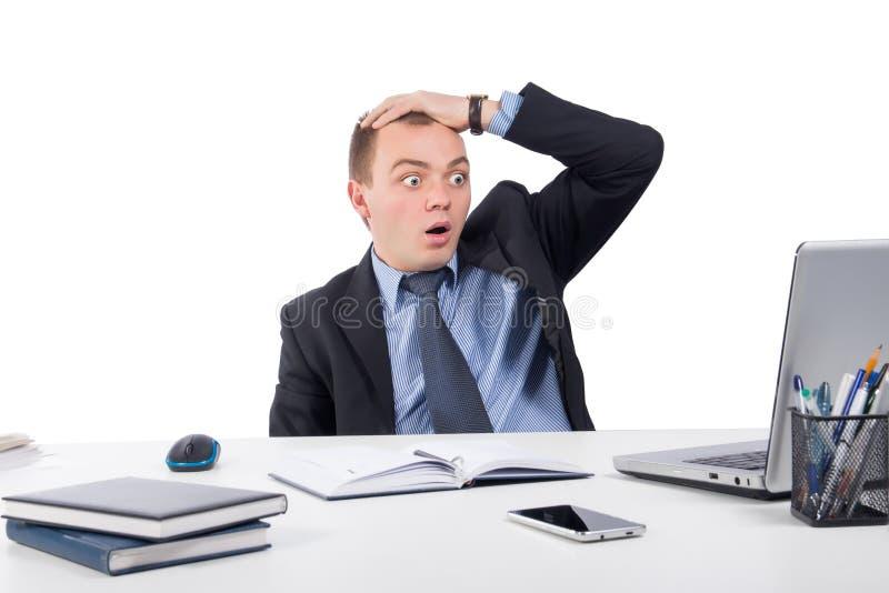Geschokte zakenman met laptop computer en documenten op kantoor royalty-vrije stock afbeelding