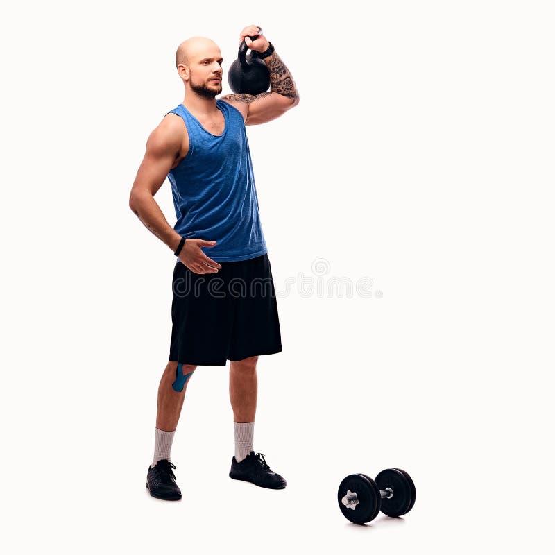Geschoren hoofd atletisch mannetje die trainingen met kettlebell doen stock fotografie
