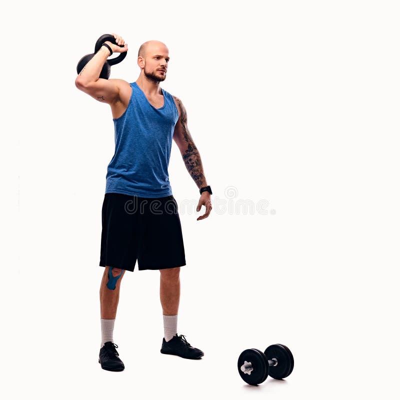 Geschoren hoofd atletisch mannetje die trainingen met kettlebell doen royalty-vrije stock afbeelding
