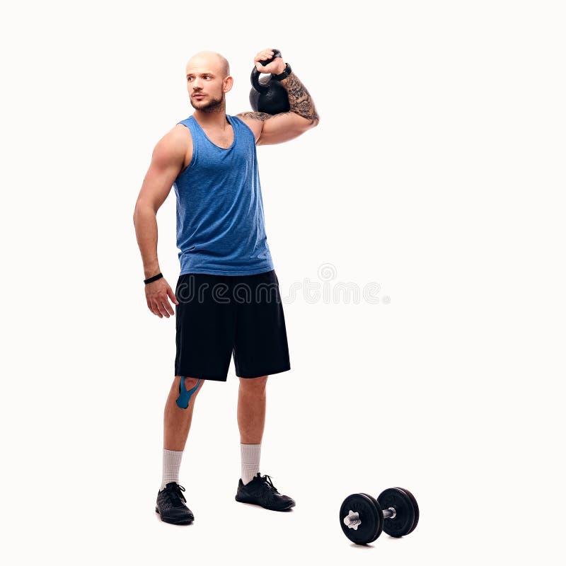 Geschoren hoofd atletisch mannetje die trainingen met kettlebell doen royalty-vrije stock foto's