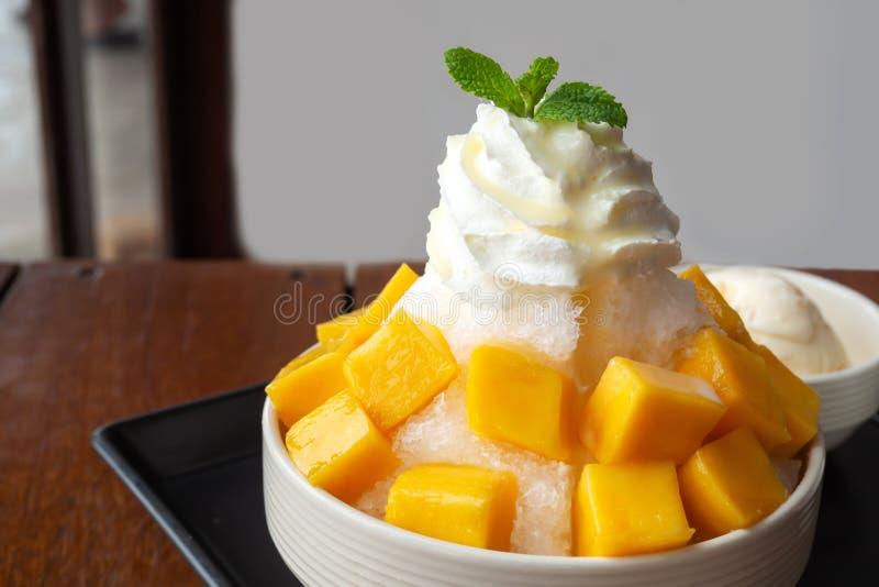 Geschoren ijsdessert met gesneden mango Gediend met vanilleroomijs en slagroom Zoet dessert in Koreaanse stijl Lokale naam stock afbeelding