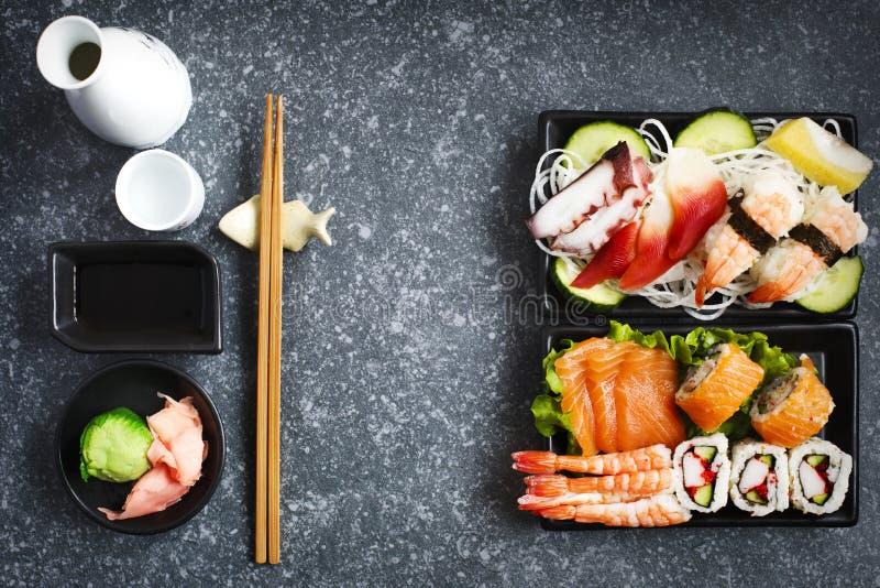 geschossen auf Schwarzem Verschiedener Sashimi, Sushi und Rollen stockfotografie