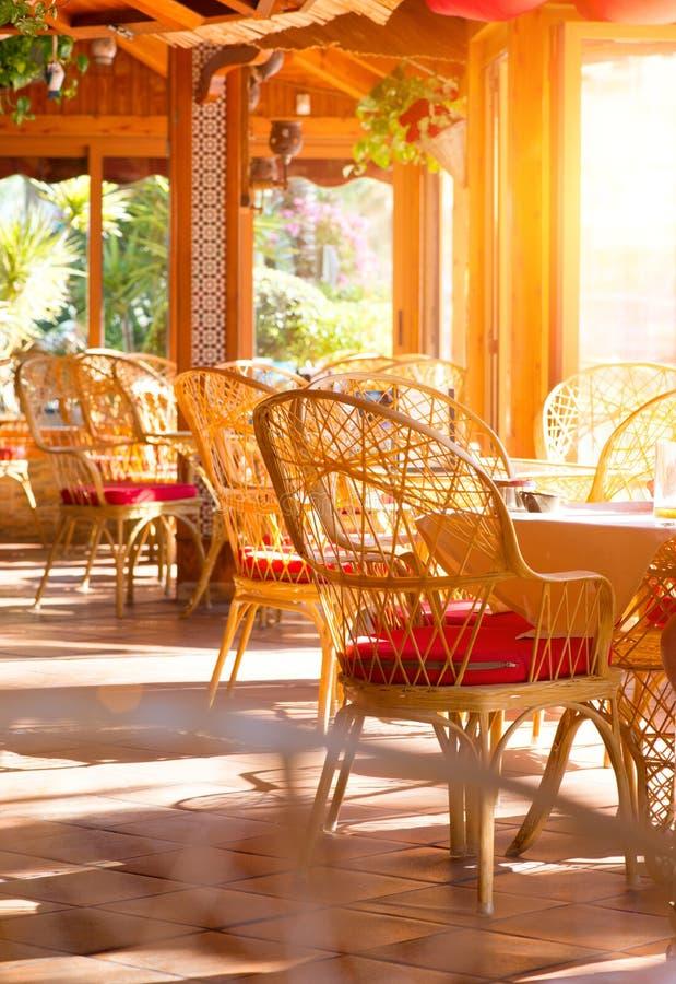 Geschossen in einem Restaurant Sommerkaffeeterrasse mit Tabellen und geflochtenen Stühlen lizenzfreie stockfotos