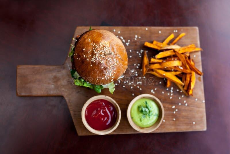 Geschossen in einem Studio Vegetarischer Burger mit Süßkartoffelfischrogen und zwei Soßen auf hölzernem Schneidebrett Geschmackvo lizenzfreie stockfotos