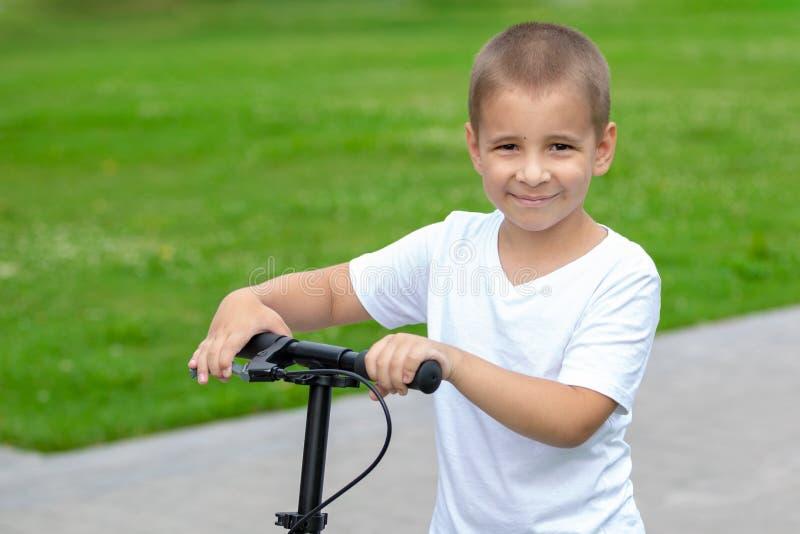 Geschossen im Studio Ein glücklicher Junge reitet einen Roller stockfotografie