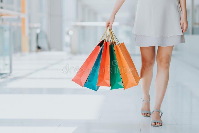 geschossen vom Bein der jungen Frau, das bunte Einkaufstaschen trägt lizenzfreies stockbild