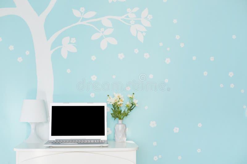 Geschossen von der modernen Laptop-Computer mit leerem Bildschirm für Ihren Text auf weißer Tabelle, Lampe und Blumen gegen die h lizenzfreies stockbild