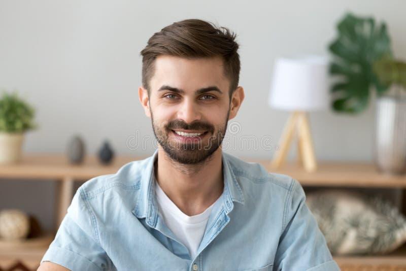 Geschossenes Hauptporträt des lächelnden erfüllten Mannes, der Kamera betrachtet stockfoto