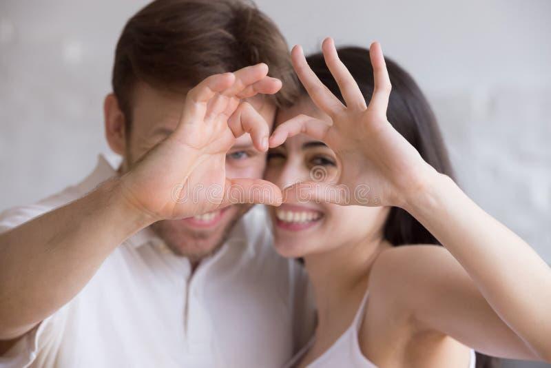 Geschossenes Hauptporträt des liebevollen glücklichen Paars Herz zeigend lizenzfreies stockbild