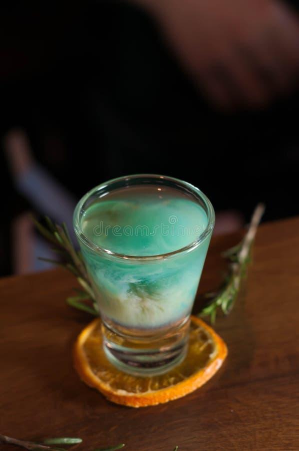 Geschoten glas met blauwe alcoholdrank op droge oranje plak met rozemarijn royalty-vrije stock foto's