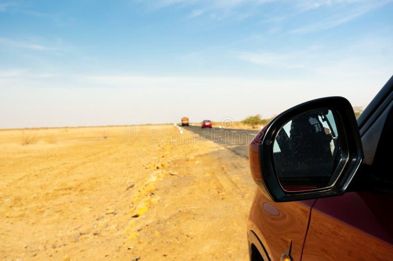 Geschoten tonend rode auto op een lange rek van lege weg in Rann van Kutch Gujarat royalty-vrije stock foto