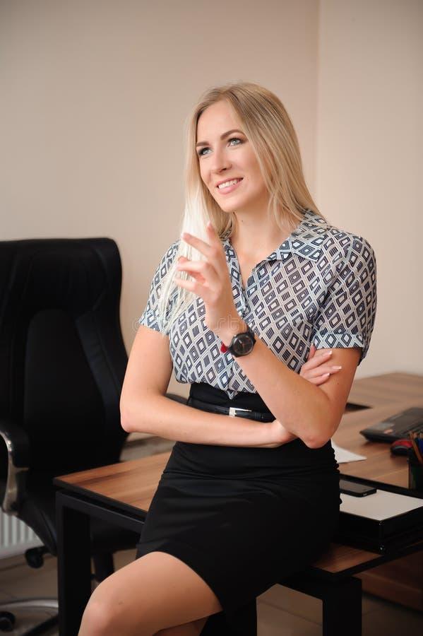 Geschoten van aantrekkelijke rijpe onderneemster die in bureau werken stock foto