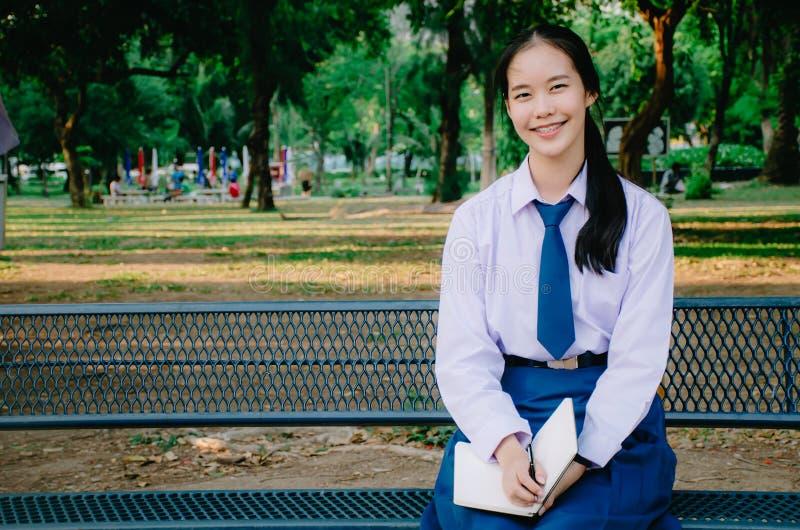 Geschoten van een boek van de de zittingslezing van de meisjesstudent op een bank in het park royalty-vrije stock afbeeldingen