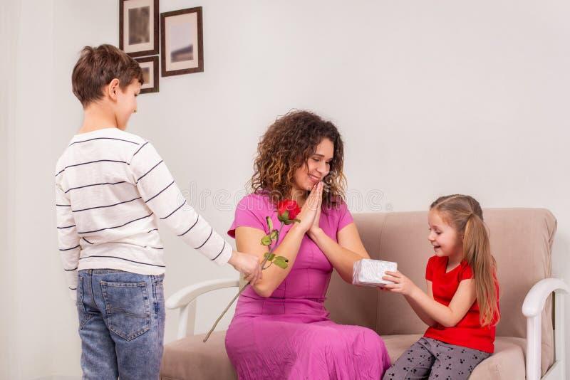 Geschoten van een moeder en haar twee kinderen die gift en bloem voor Moederdag of haar verjaardag houden royalty-vrije stock foto's