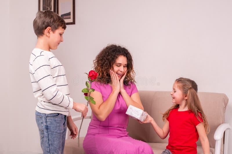Geschoten van een moeder en haar twee kinderen die gift en bloem voor Moederdag of haar verjaardag houden stock foto's