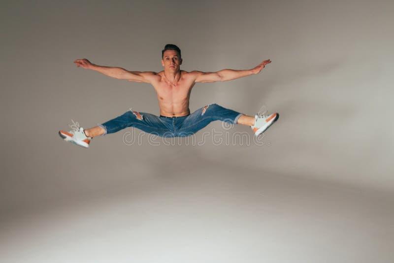 Geschoten van gekke, gekke, vrolijke, succesvolle, gelukkige kerel in toevallige uitrusting, jeans, die met omhoog handen springe stock foto