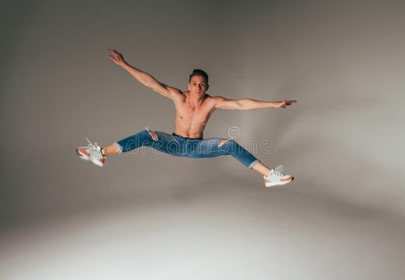 Geschoten van gekke, gekke, vrolijke, succesvolle, gelukkige kerel in toevallige uitrusting, jeans, die met omhoog handen springe stock afbeeldingen