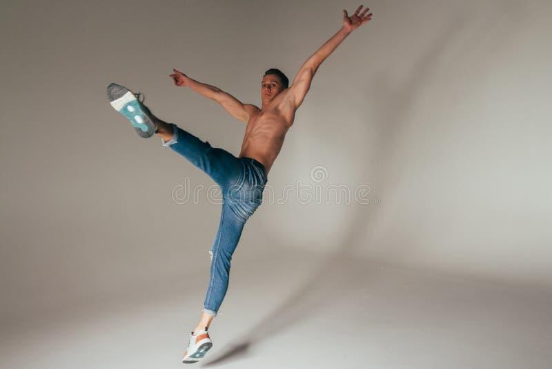 Geschoten van gekke, gekke, vrolijke, succesvolle, gelukkige kerel in toevallige uitrusting, jeans, die met omhoog handen springe stock foto's