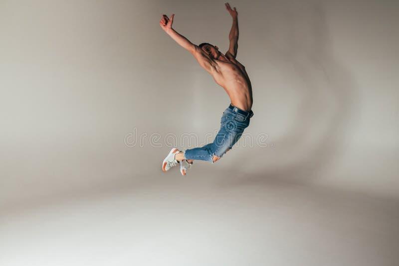 Geschoten van gekke, gekke, vrolijke, succesvolle, gelukkige kerel in toevallige uitrusting, jeans, die met omhoog handen springe royalty-vrije stock afbeeldingen