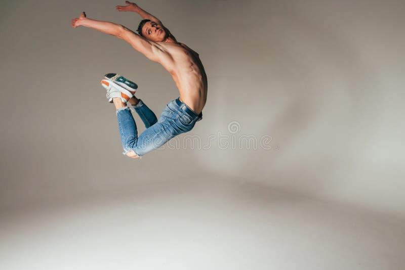 Geschoten van gekke, gekke, vrolijke, succesvolle, gelukkige kerel in toevallige uitrusting, jeans, die met omhoog handen springe royalty-vrije stock foto's