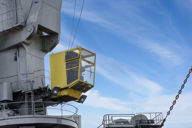 Geschoten van gele controlecabine met arbeider De oude, roestige, grijze opheffende lading van de havenkraan in schip op duidelij stock foto's