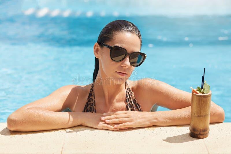 Geschoten van het overweldigende mooie jonge vrouw genieten die in pool met vers fruitcocktail zonnebaden, vrolijke aantrekkelijk stock foto