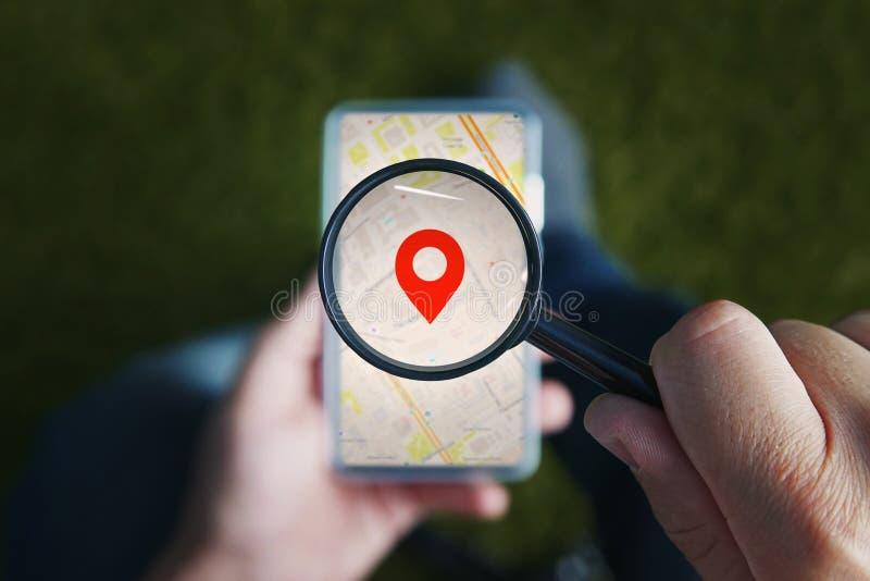 Geschoten van mannelijke handen die vergrootglas met het rode pictogram van Geo-plaats houden en door het aan smartphone kijken royalty-vrije stock fotografie