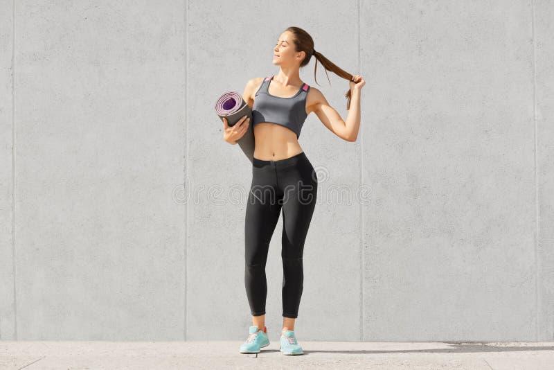 geschoten van slanke mooie sportvrouw met sportief lichaam draagt de vorm, sportkleding, houdt poneystaart, die naar geschiktheid stock afbeeldingen