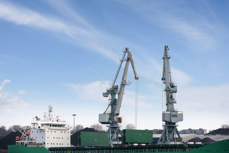 Geschoten van twee oude, roestige, grijze havenkranen met grote haken, opheffende lading in schip op duidelijke blauwe hemelachte royalty-vrije stock afbeelding